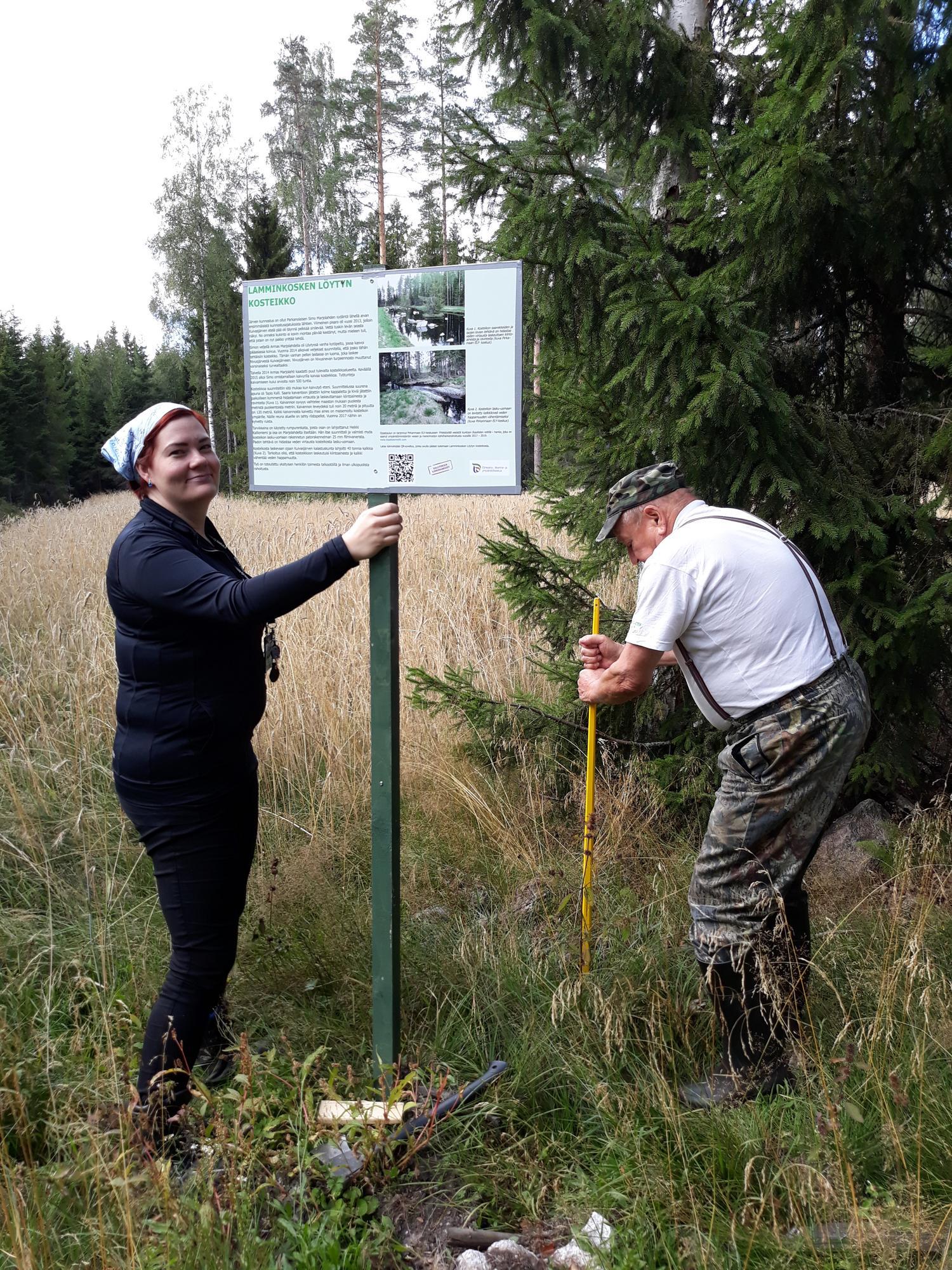 Pirkanmaan ELY-keskuksen projektiasiantuntija Virve Rinnola pitelee kosteikosta kertovaa opastaulua, kosteikon toteuttaja, maanomistaja Simo Marjolahti.