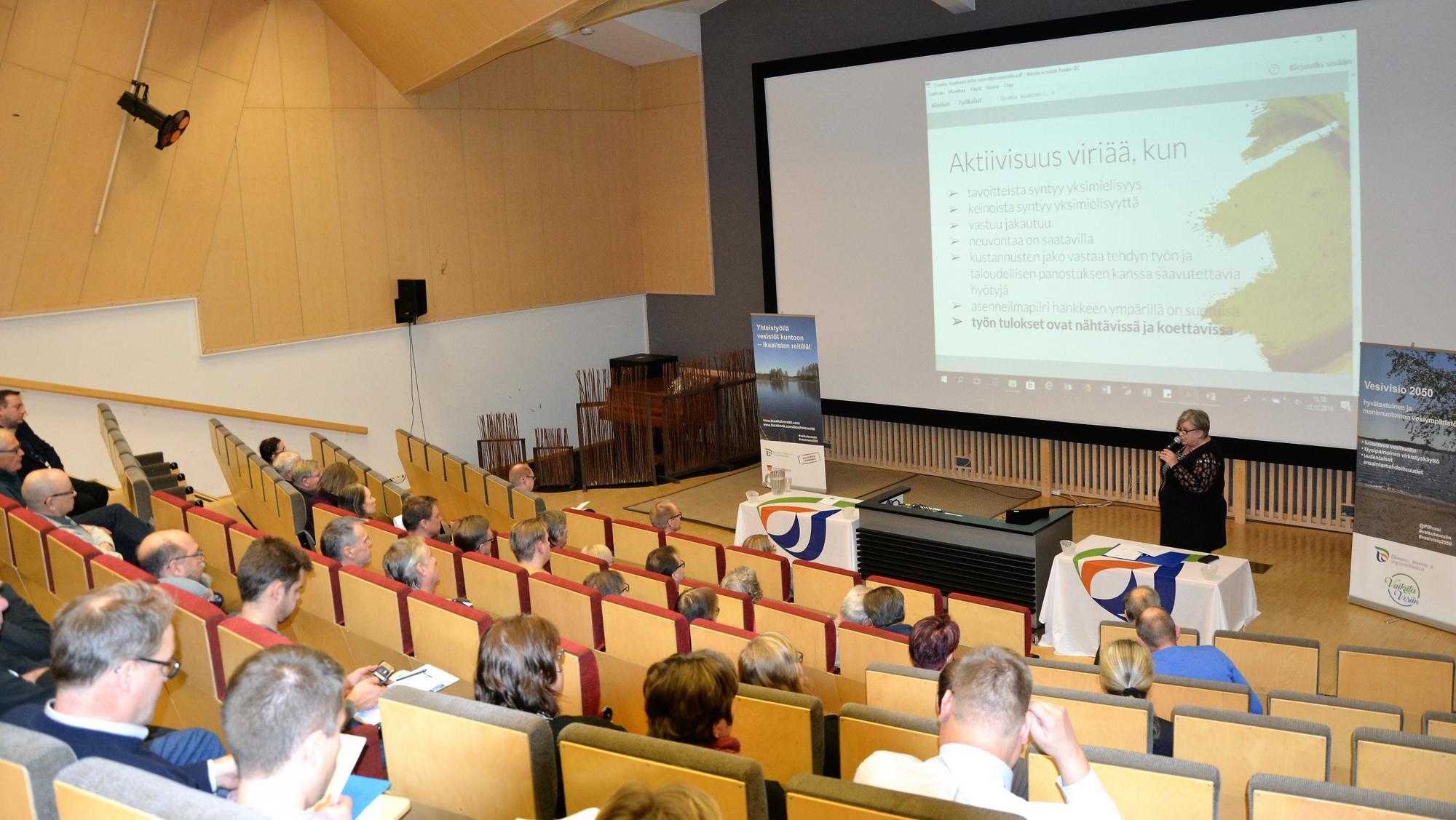 Neuvottelukunnan jäsenistöä auditoriossa seuraamassa Arja Pihlajan esitystä.